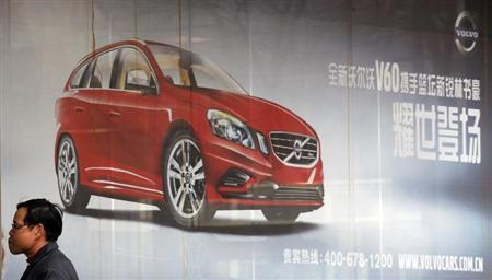 Man walks past a Volvo advertisement in Beijing
